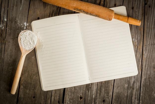 Pieczenia w tle. narzędzia i składniki do pieczenia na starym rustykalnym drewnianym stole. zarezerwuj notatnik z przepisami. widok z góry