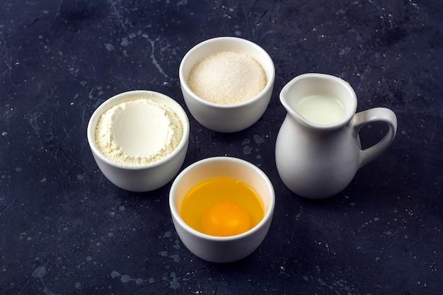Pieczenia w tle. składniki do gotowania ciasta w miskach na ciemnym stole. koncepcja żywności. ścieśniać