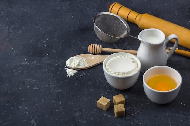 Pieczenia w tle. składniki i przybory do gotowania ciasta na ciemnym stole. koncepcja żywności.