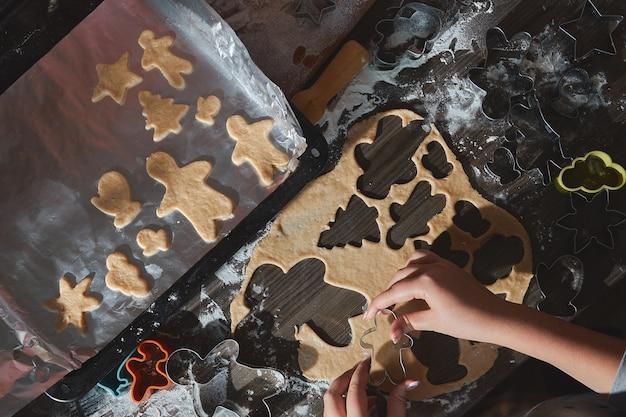 Pieczenie ciasteczek świątecznych na ciemnym brązowym drewnianym stole. rodzina co piernika, krojenie ciasteczek z piernika, widok z góry.