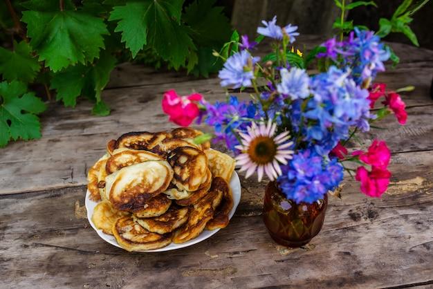 Pieczenie i jagody na drewnianym tle z kwiatami.
