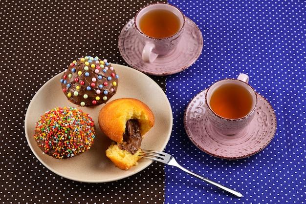Pieczenie z herbatą i czekoladą na stole. dwie filiżanki herbaty z babeczkami i czekoladą z wielokolorowym proszkiem na stole.