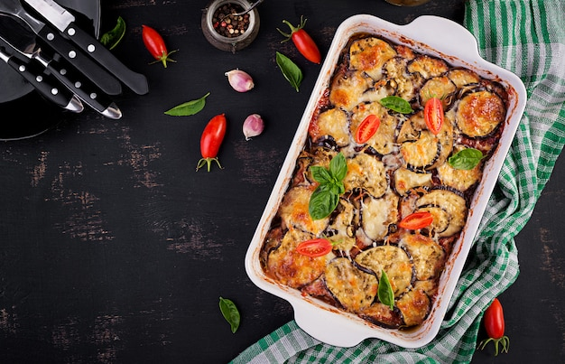 Pieczona bakłażan z serem na ciemnym drewnianym stole. parmigiana melanzane. widok z góry. kuchnia włoska.