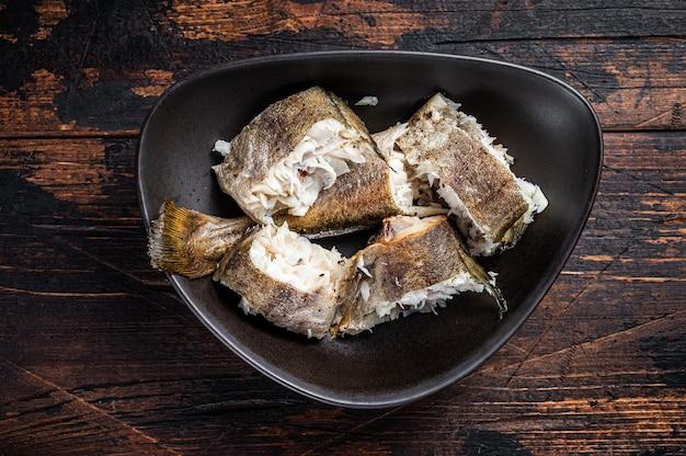 Pieczona biała ryba morszczuka w talerzu. ciemne drewniane tło. widok z góry.