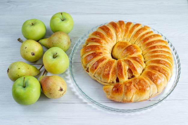 Pieczona bransoletka z pysznego ciasta uformowana wewnątrz szklanego talerza wraz z jabłkami i gruszkami na białym biurku, ciastko biszkoptowe słodkie zapiekanka