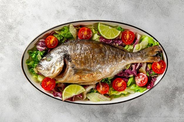 Pieczona cała ryba dorado na talerzu ze świeżymi warzywami na jasnoszarym tle widok z góry z bliska