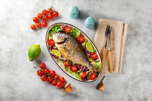 Pieczona cała ryba dorado na talerzu ze świeżymi warzywami na jasnoszarym tle widok z góry