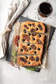 Pieczona focaccia z pomidorami, czarnymi oliwkami i rozmarynem. naturalny włoski chleb domowej roboty. widok z góry.