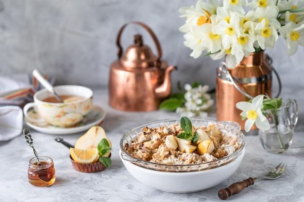 Pieczona gruszka kruszona z gruszkami i miodem w białym naczyniu na stole z miedzianymi naczyniami i kwiatami