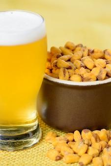 Pieczona i solona kukurydza w ceramicznym garnku nad żółtą jutą i szklanką zimnego piwa