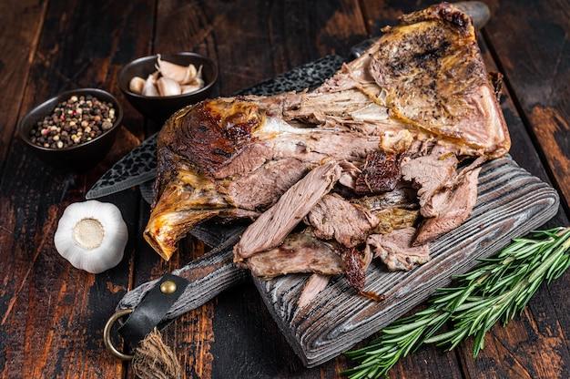 Pieczona jagnięcina baranina krojenia mięsa łopatki na drewnianej desce. ciemne drewniane tło. widok z góry.