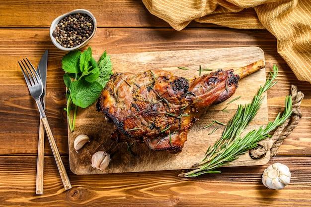 Pieczona jagnięcina, owcza noga na desce do krojenia z rozmarynem