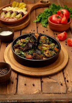 Pieczona jagnięcina w żeliwnej misce ozdobiona świeżymi ziołami