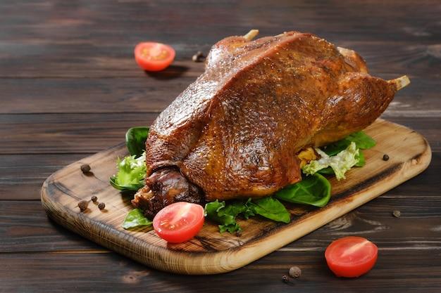 Pieczona kaczka i warzywa na ciemnej drewnianej desce