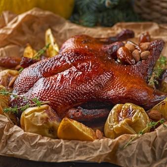 Pieczona kaczka nadziewana pomarańczami i rozmaryną. świąteczny stół. czarne tło.