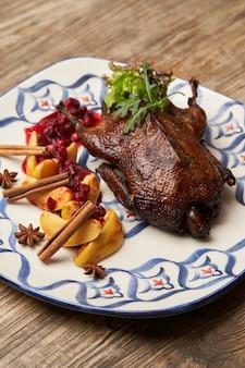 Pieczona kaczka z pigwą na tle drewniany stół. pieczona cała kaczka z sosem pigwowo-jagodowym.