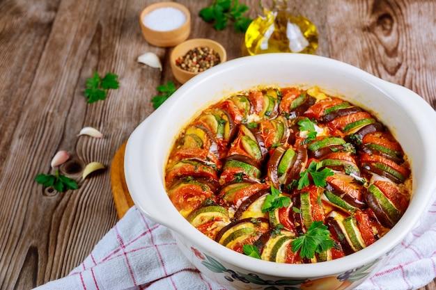 Pieczona kolorowa ratatouille warzywna z serem mozzarella w białej patelni piekarnika