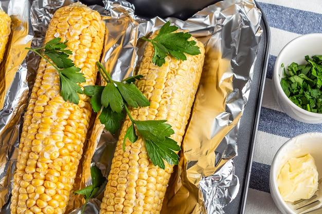 Pieczona kukurydza z solą, masłem i kolendrą lub pietruszką w folii na kuchennym stole
