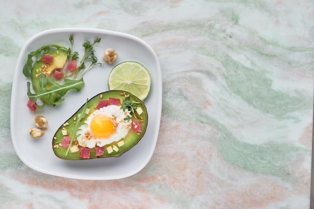 Pieczona łódka awokado z kostkami szynki, jajkiem przepiórczym i serem podana z zieloną sałatą z rukoli