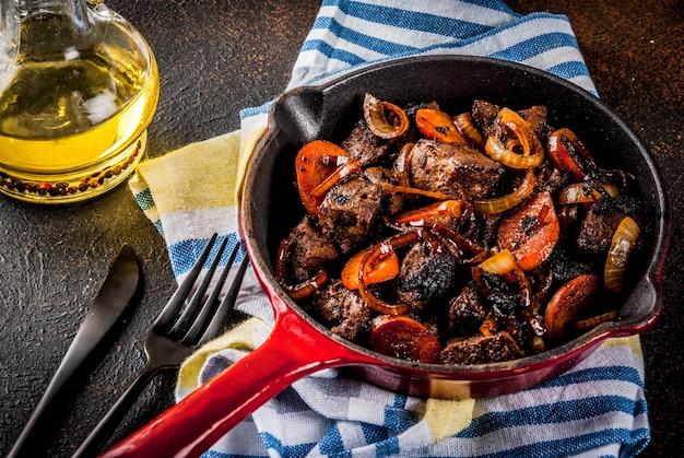 Pieczona lub grillowana wątroba wołowa z cebulą i marchewką na porcji patelni, ciemny zardzewiały stół