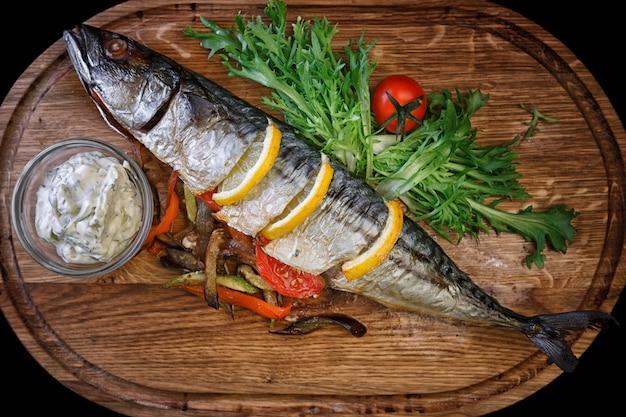 Pieczona makrela z cytryną, warzywami i przyprawami, na drewnianej desce z białym sosem, ziołami i pomidorkami cherry