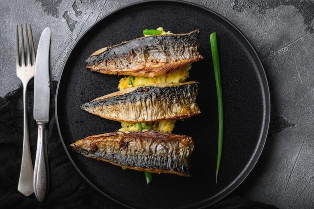 Pieczona makrela z puree ziemniaczanym na szarym tle z teksturą, widok z góry.