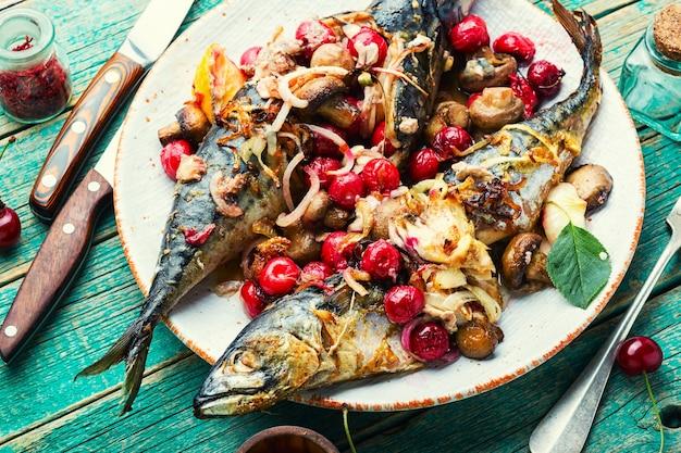 Pieczona makrela z sosem wiśniowym.ryba nadziewana jagodami.garnica na talerzu