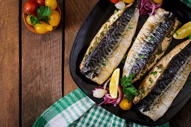 Pieczona makrela z ziołami i przyozdobiona cytryną i marynowanymi warzywami. widok z góry