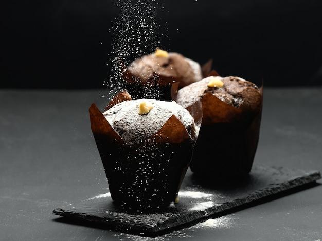 Pieczona muffinka czekoladowa na czarnym stole posypana cukrem pudrem, pyszny deser, zbliżenie