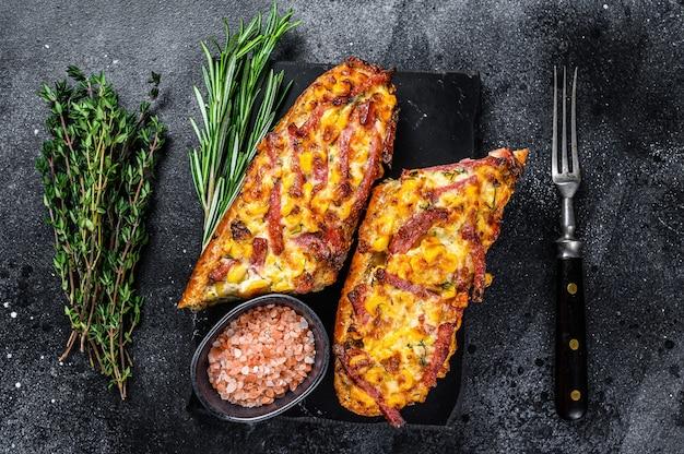 Pieczona na gorąco otwarta kanapka baguette z szynką, boczkiem, warzywami i serem. czarne tło. widok z góry.