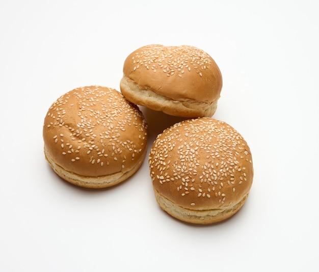 Pieczona okrągła bułka ze świeżej białej mąki pszennej posypana sezamem na białym stole. bułka do hamburgerów, cheesebergerów i kanapek