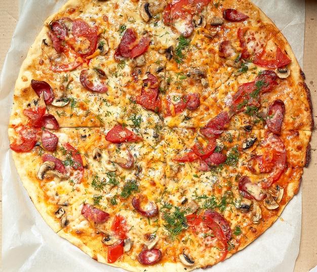 Pieczona okrągła pizza z wędzonymi kiełbasami, pieczarkami, pomidorami, serem i koperkiem w otwartym kartonowym pudełku