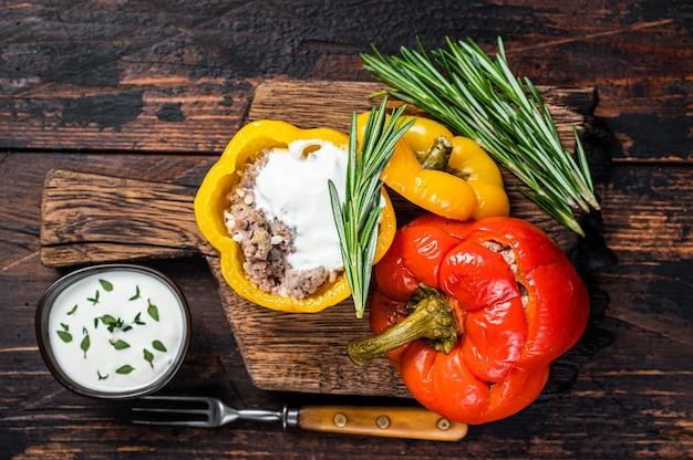Pieczona papryka faszerowana mięsem wołowym, ryżem i warzywami na drewnianej desce