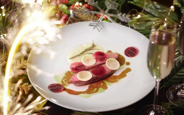 Pieczona pierś z kaczki z burakami daikon i białym sosem na tle świątecznej dekoracji