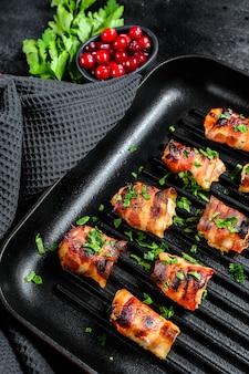 Pieczona pierś z kurczaka owinięta boczkiem na patelni.