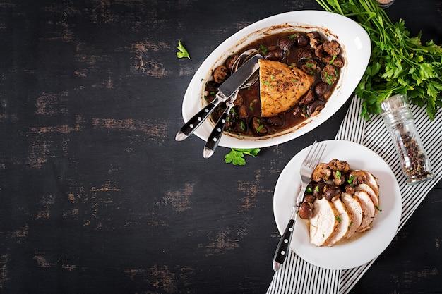 Pieczona pierś z kurczaka z pieczarkami w sosie balsamicznym na stole.