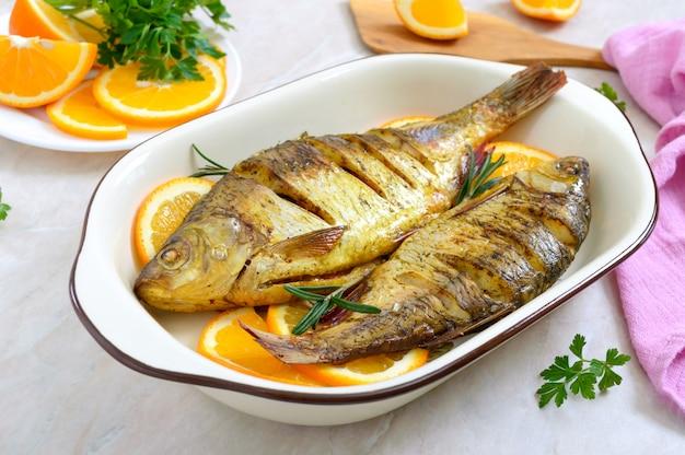 Pieczona płoć ryba z warzywami i pomarańczami w ceramicznej misce. menu dietetyczne