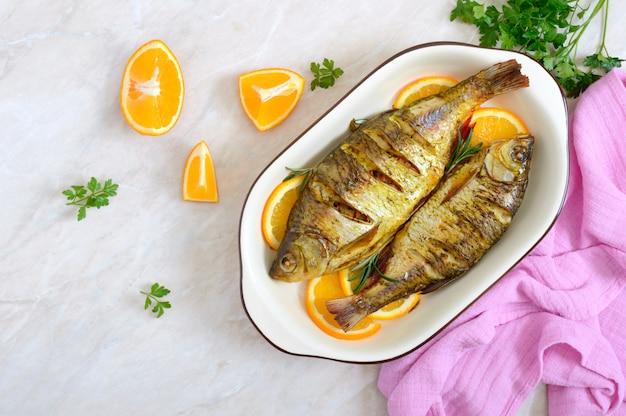 Pieczona płoć ryba z warzywami i pomarańczami w ceramicznej misce. widok z góry. menu dietetyczne.