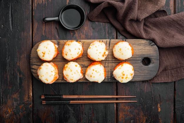 Pieczona rolka sushi z kapslem z krewetkami i kawiorem masago. zestaw tradycyjnych dań restauracji sushi, na starym ciemnym drewnianym stole
