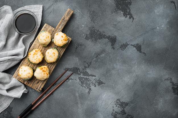 Pieczona rolka sushi z kapslem z krewetkami i kawiorem masago. zestaw tradycyjnych dań restauracji sushi na szarym kamieniu