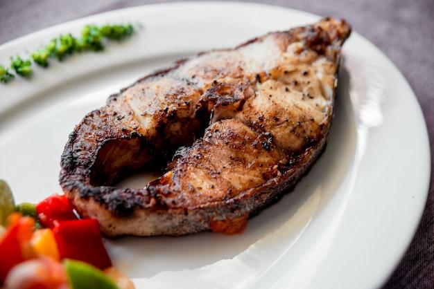 Pieczona ryba na białym talerzu.