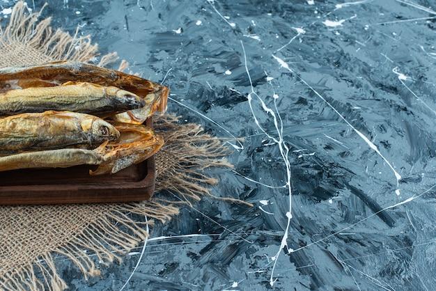 Pieczona ryba na desce na fakturze, na niebieskim tle.