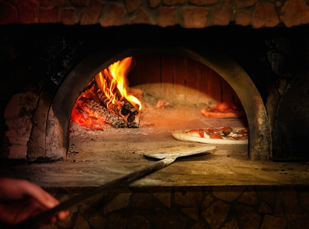 Pieczona smaczna pizza margherita wydostająca się z piekarnika