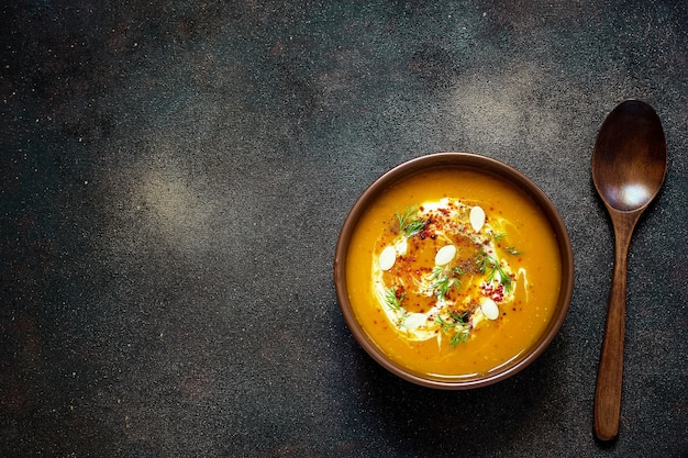 Pieczona zupa dyniowa i marchewkowa ze śmietaną, nasionami i świeżą zielenią w ceramicznej misce. widok z góry