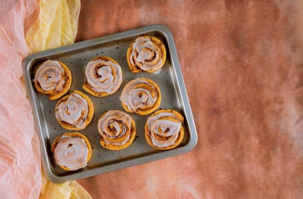 Pieczone bułeczki cynamonowe na stalowej blasze do pieczenia.