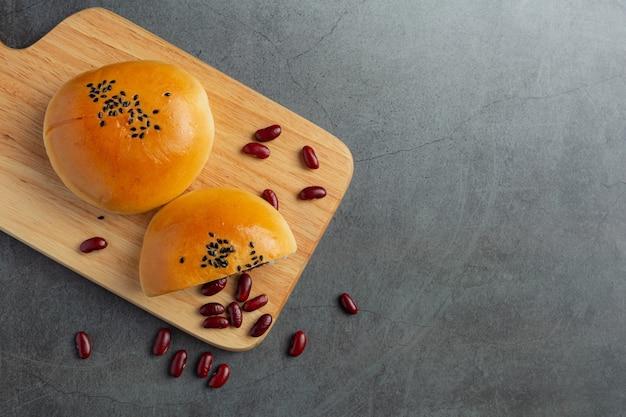Pieczone bułeczki z czerwoną fasolą na drewnianej desce do krojenia