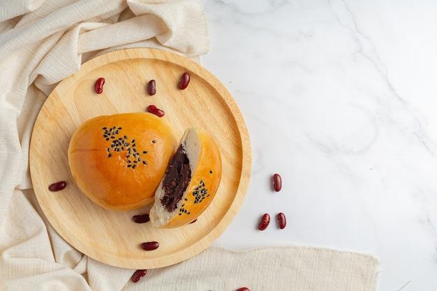 Pieczone bułeczki z czerwoną fasolą na drewnianym talerzu