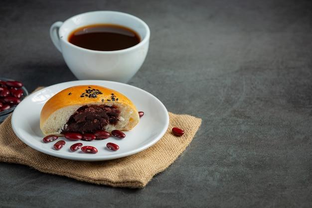 Pieczone bułeczki z pasty fasolowej układane na brązowym materiale podawane z kawą