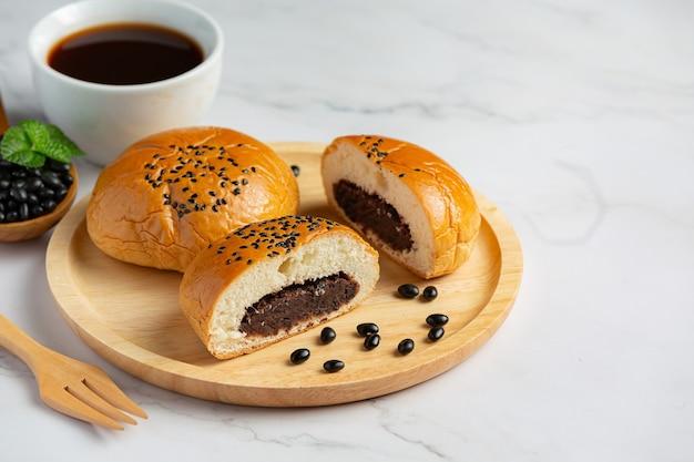 Pieczone bułeczki z pasty z czarnej fasoli na drewnianym talerzu podawane z kawą
