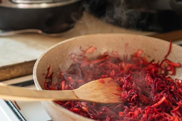 Pieczone buraki, marchewkę i cebulę na patelni na kuchence. gotowanie barszczu dla rodziny w zwykłej rodzinie.